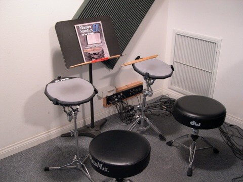 drum lessons practice set showing two seats and practice pads, drum sticks and study sheet
