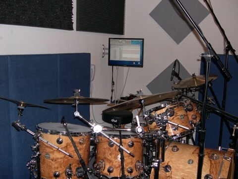 studio drums with cymbals, microphones, monitor, and foam paddings